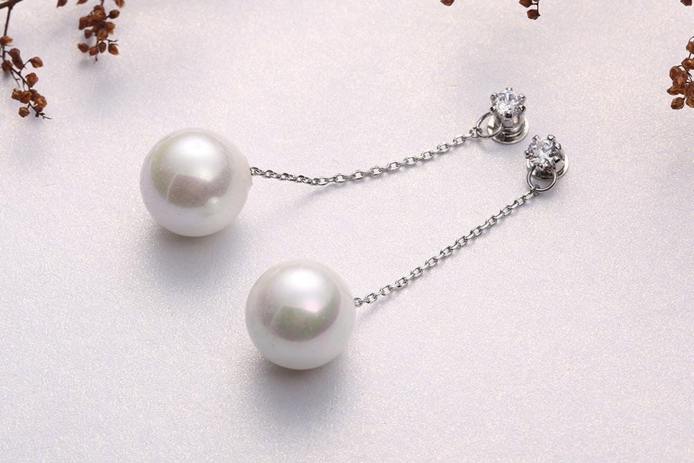 簡約高雅珍珠鋯鑽 耳針/黏式耳環,桌上展示。