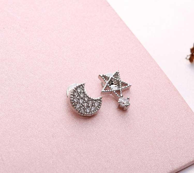 精巧可愛不對稱月亮小星星鋯鑽 耳針/黏式耳環,桌上展示。