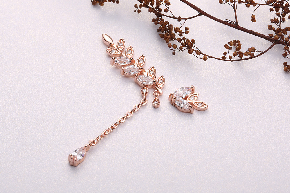 優雅水鑽月桂葉不對稱 耳針/黏式耳環,桌上展示。