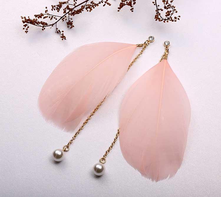 優雅氣質民族風珍珠羽毛長款 耳針/黏式耳環,桌上展示。