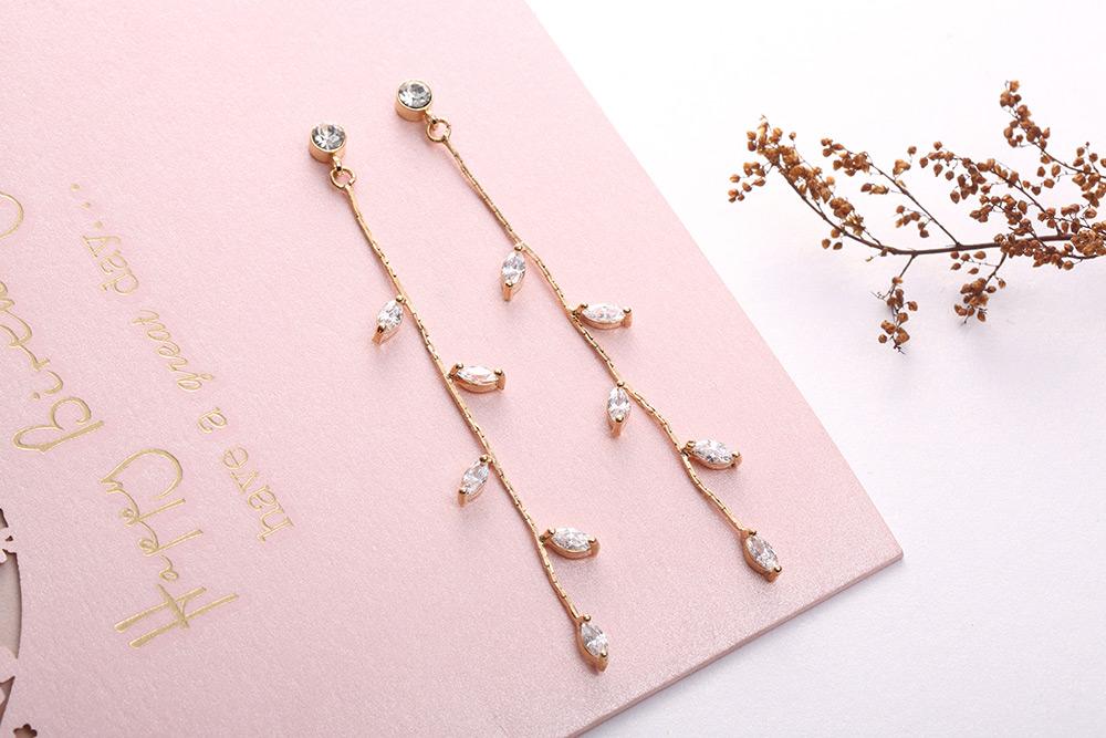 精巧迷人水鑽嫩葉鍍金黏式耳環,桌上展示。