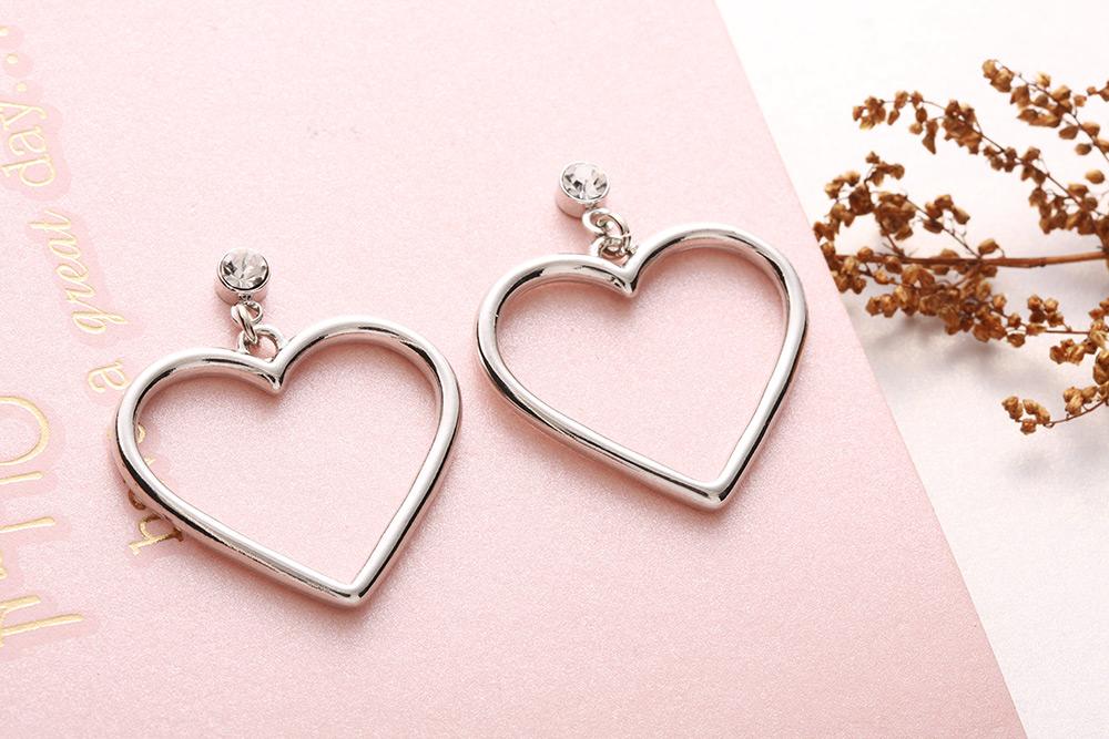 清新簡約簍空桃心 耳針/黏式耳環,桌上展示。
