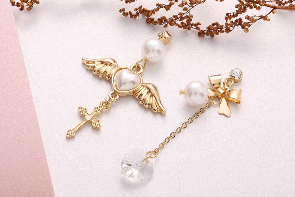 天使翅膀桃心十字架水晶玻璃不對稱黏式耳環,桌上展示。