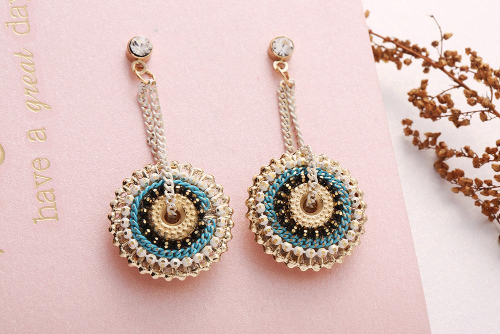 波西米亞風圓形鍊條 耳針/黏式耳環,桌上展示。