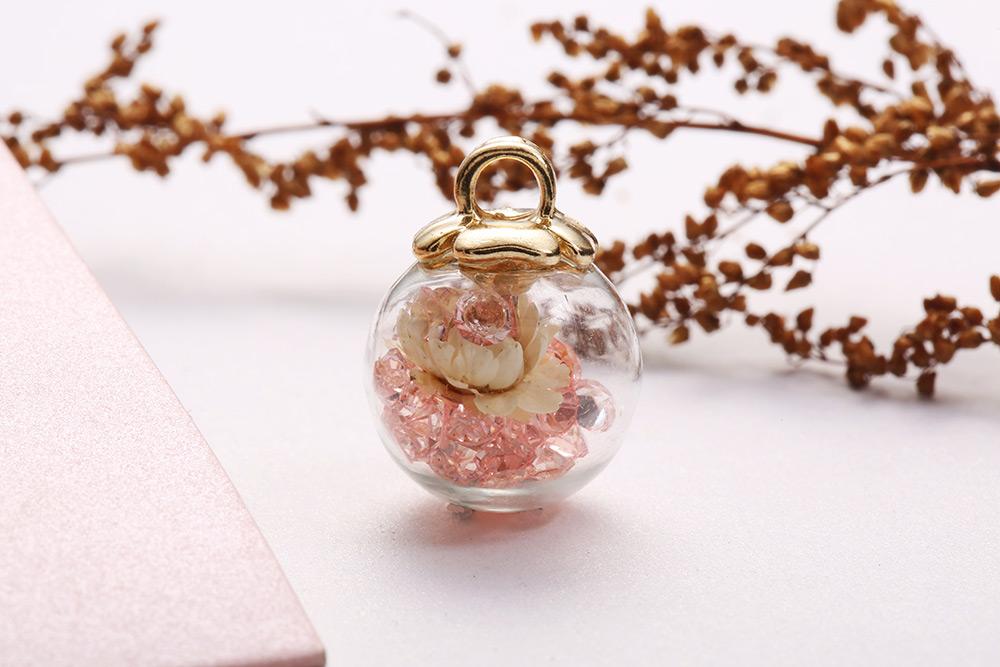 彩色水晶透明玻璃球乾花黏式耳環,桌上展示。