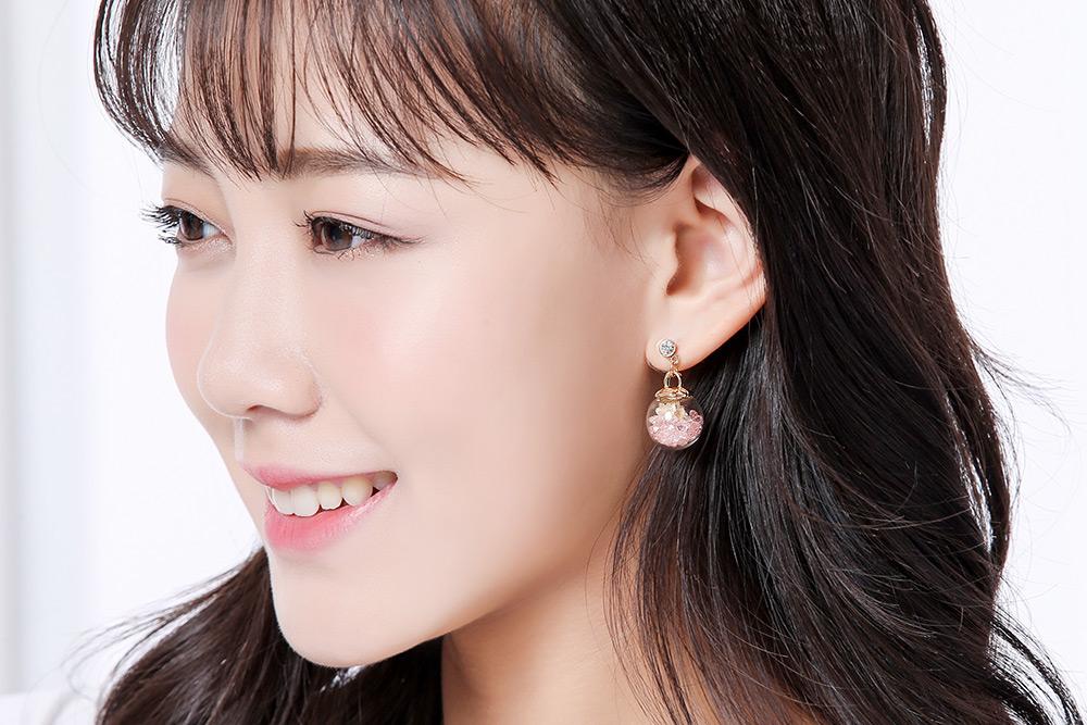 模特兒配戴展示:美麗的乾花保存在透明的玻璃球裡,彩色水晶的陪襯,讓花更加夢幻動人,創新的黏貼式耳環,不必擔心長時間配戴耳夾的不舒服感。