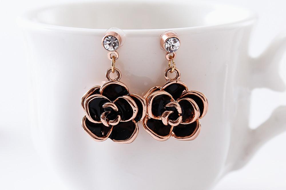 典雅鍍金黑玫瑰 耳針/黏式耳環,桌上展示。