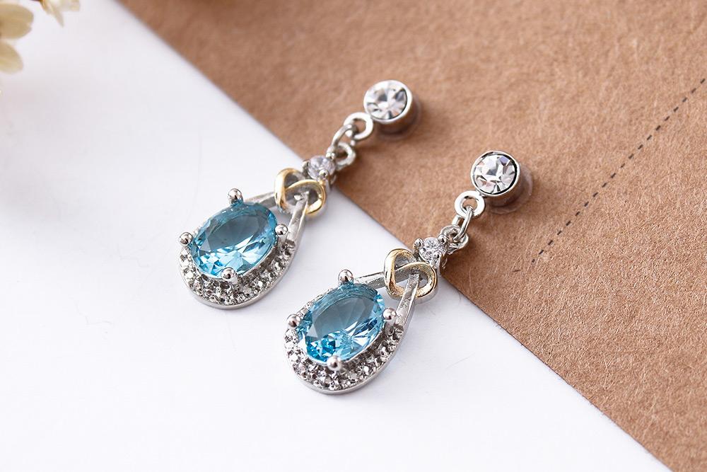 蔚藍之心水滴亮鑽 耳針/黏式耳環,桌上展示。