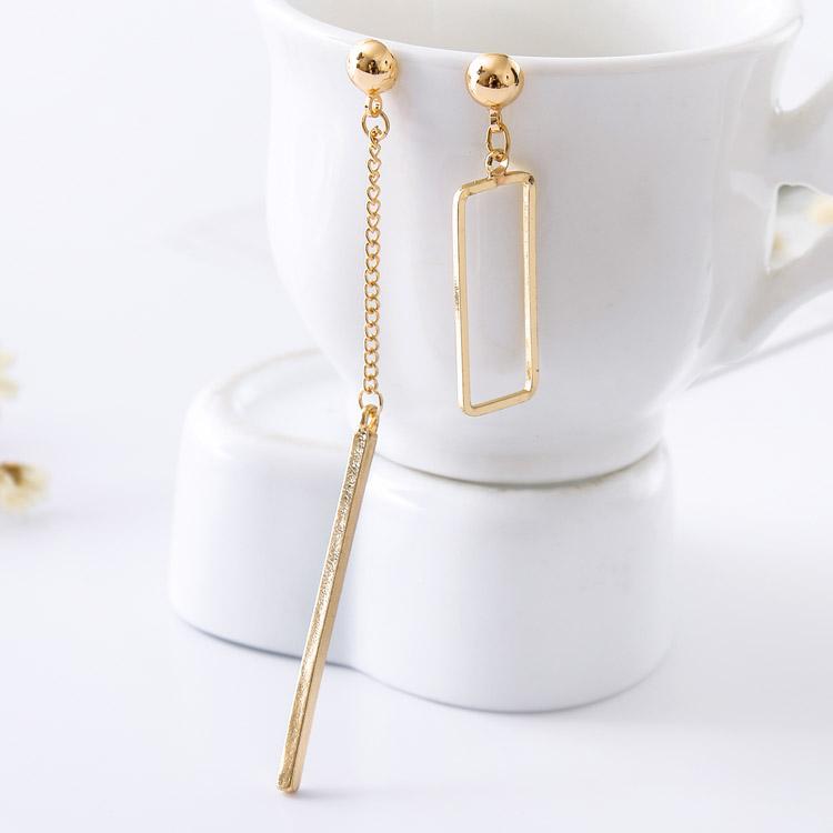 獨特個性一字墜簍空不對稱 耳針/黏式耳環,桌上展示。