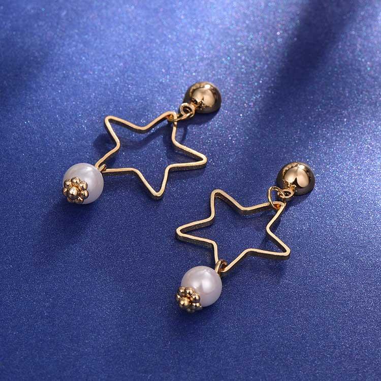童趣簍空星星珍珠黏式耳環,桌上展示。