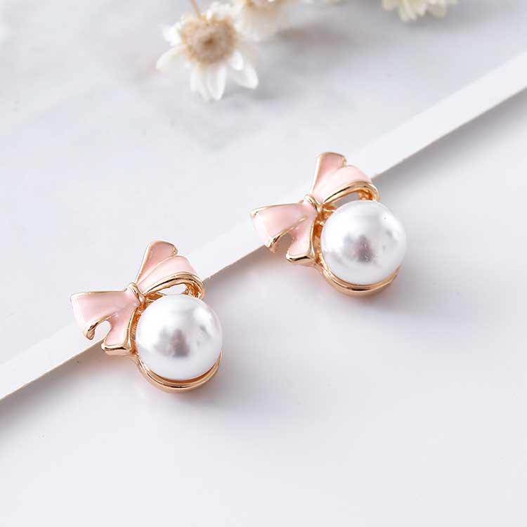 甜美可愛蝴蝶結珍珠 耳針/黏式耳環,桌上展示。