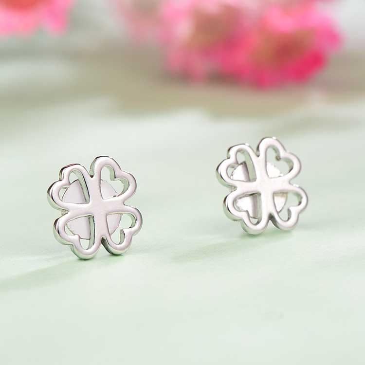 可愛簍空四葉草黏式耳環,桌上展示。