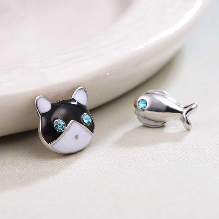 貓與小魚不對稱黏式耳環,桌上展示。