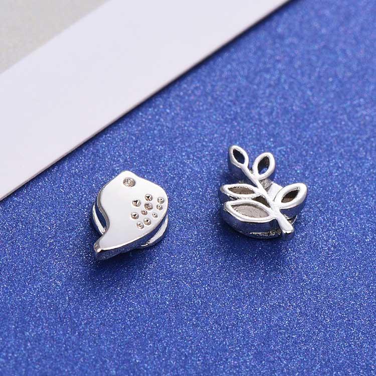 小雞與嫩葉不對稱 耳針/黏式耳環,桌上展示。