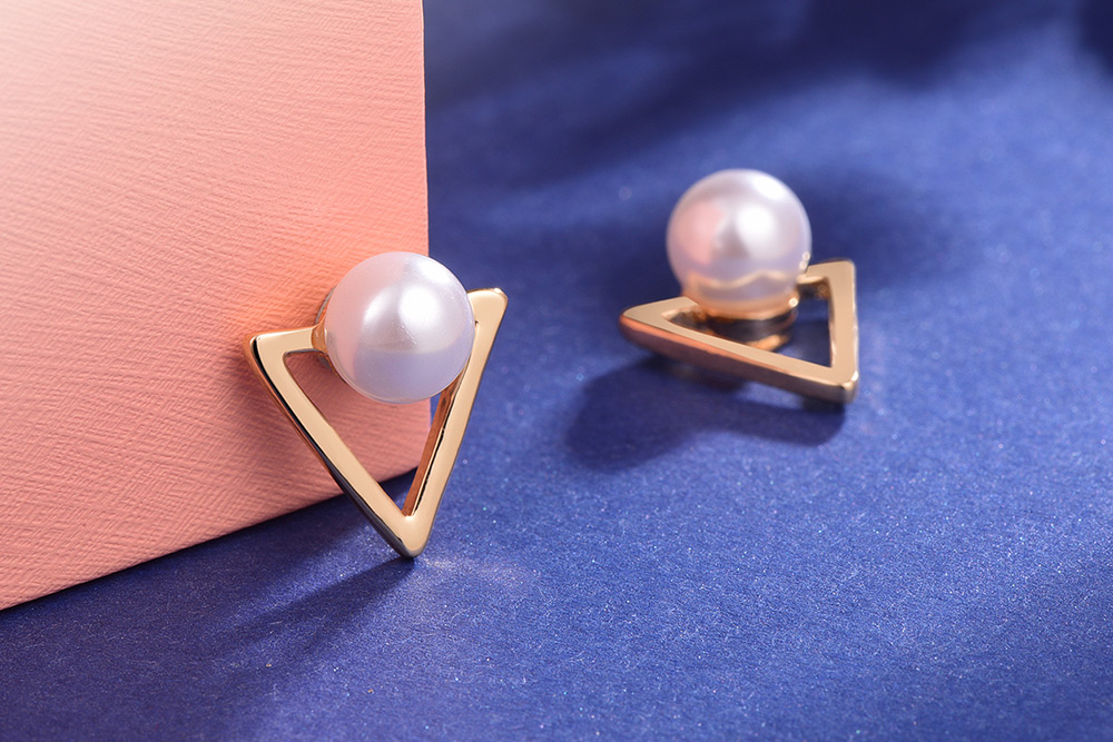 簍空金三角珍珠 耳針/黏式耳環,桌上展示。