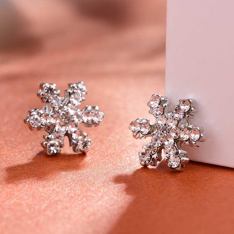 可愛亮麗滿鑽雪花黏式耳環,桌上展示。
