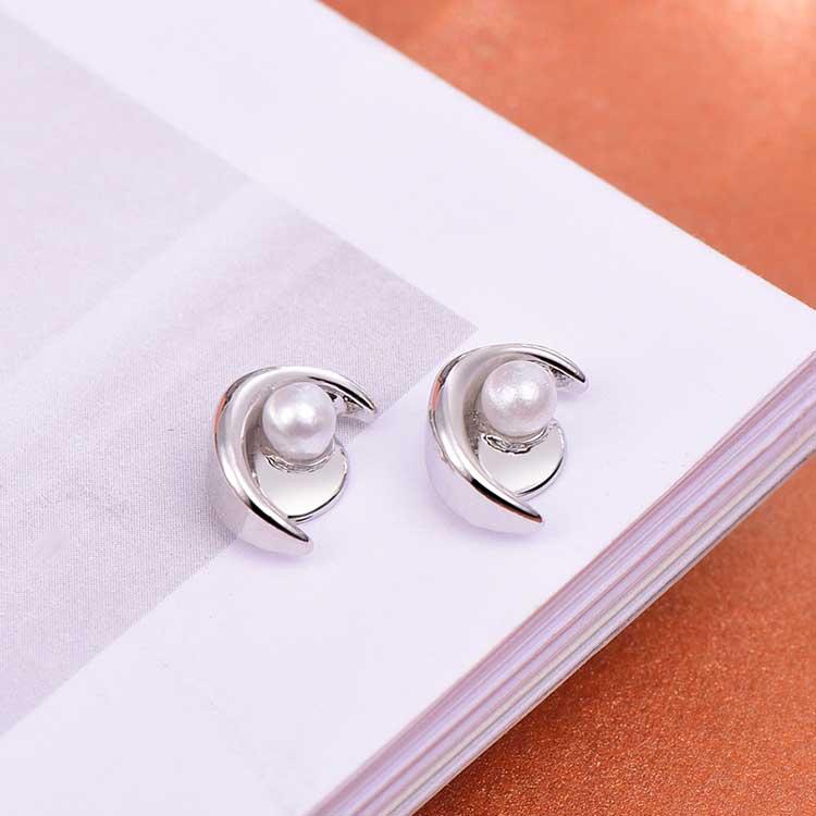 月牙彎彎珍珠 耳針/黏式耳環,桌上展示。