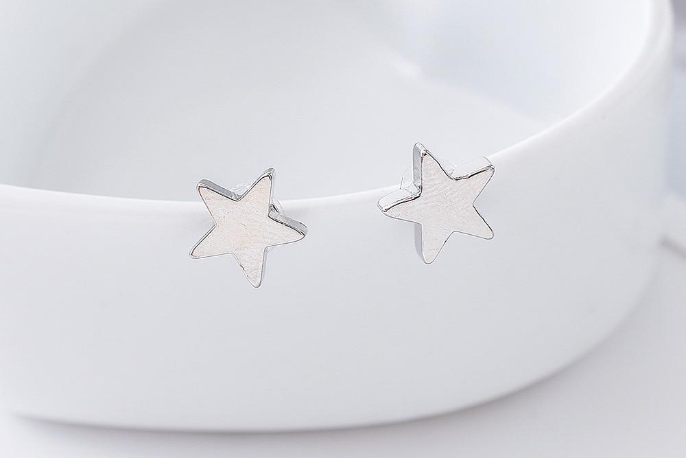 簡約小巧五角星黏式耳環,桌上展示。