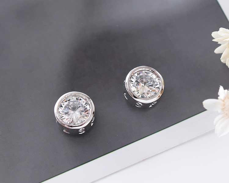 個性韓流圓形鑲鑽黏式耳環,桌上展示。