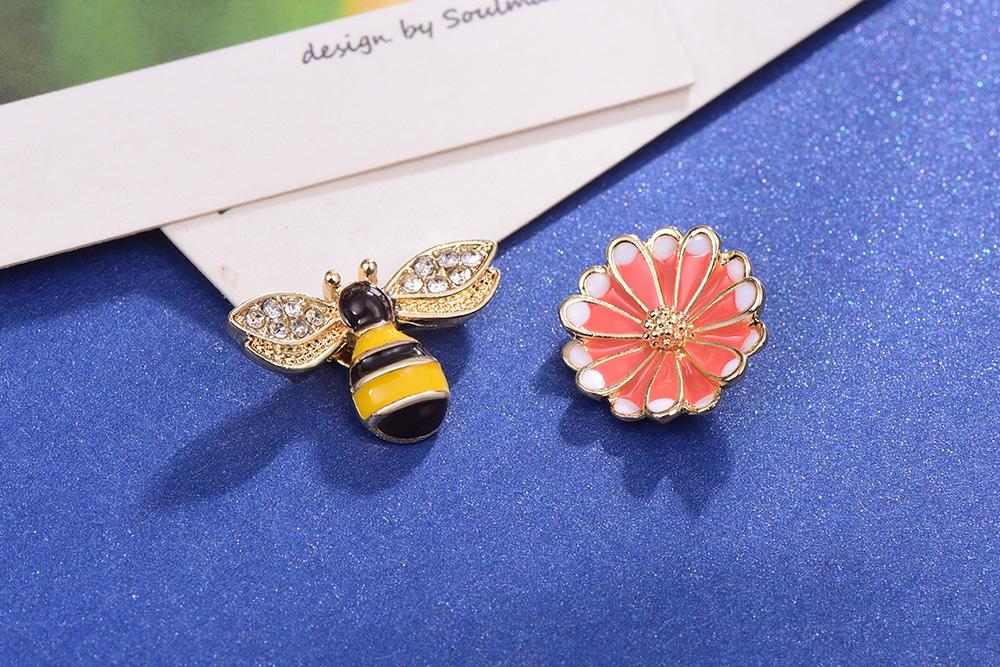甜美小蜜蜂雛菊不對稱 耳針/黏式耳環,桌上展示。