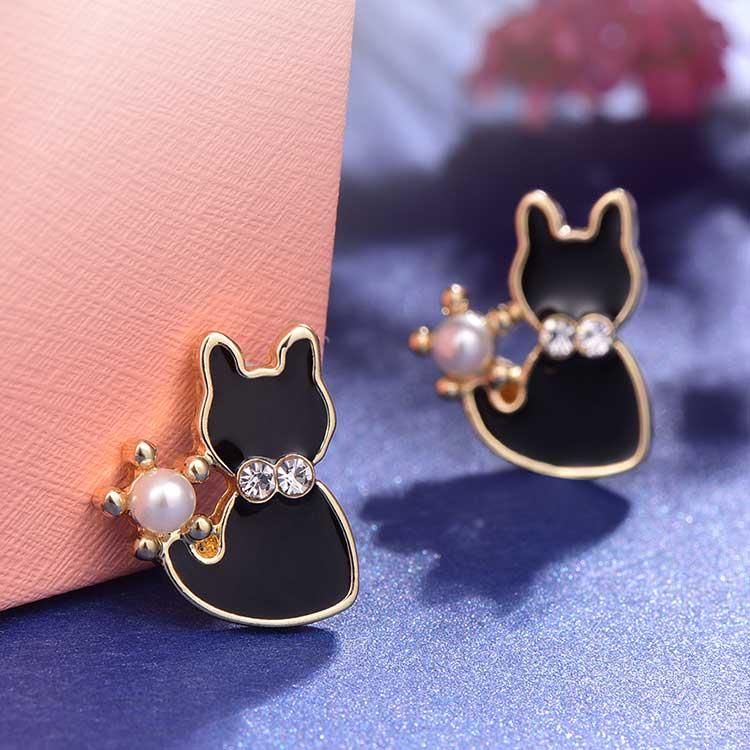 優雅珍珠小黑貓 耳針/黏式耳環,桌上展示。
