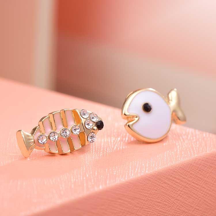 萌趣小魚與魚骨頭不對稱耳針/黏式耳環,桌上展示。