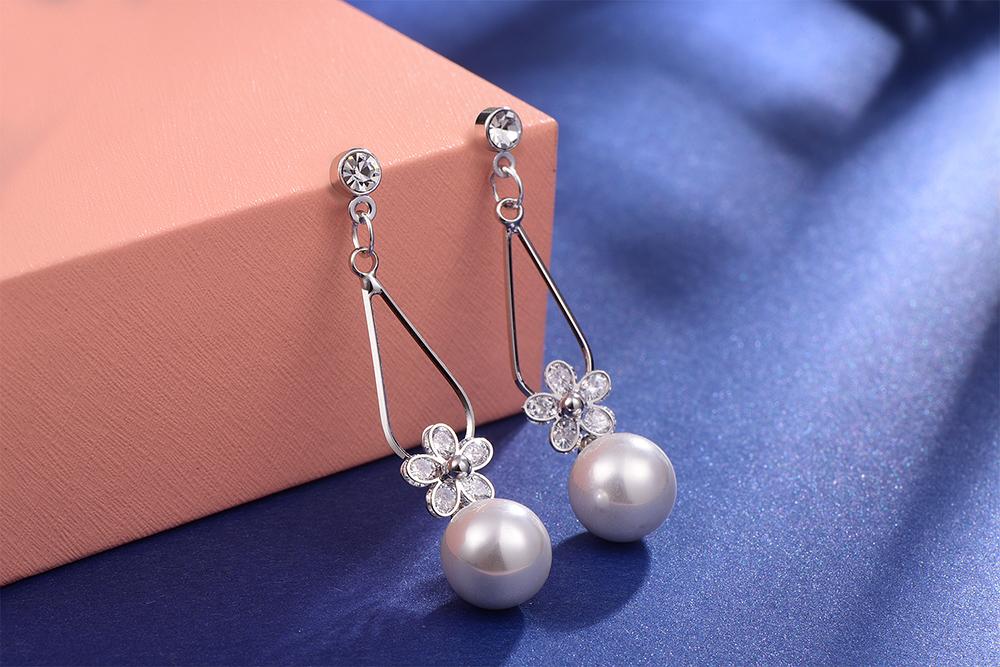 清晰氣質珍珠水滴花瓣 耳針/黏式耳環,桌上展示。
