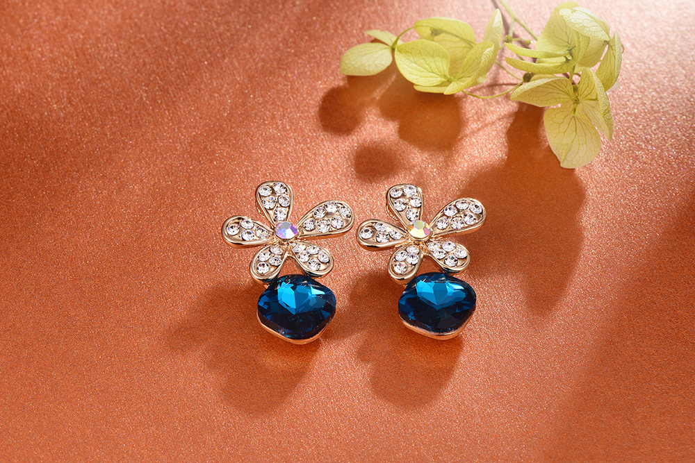 耀眼鑲鑽水晶花朵 耳針/黏式耳環,桌上展示。