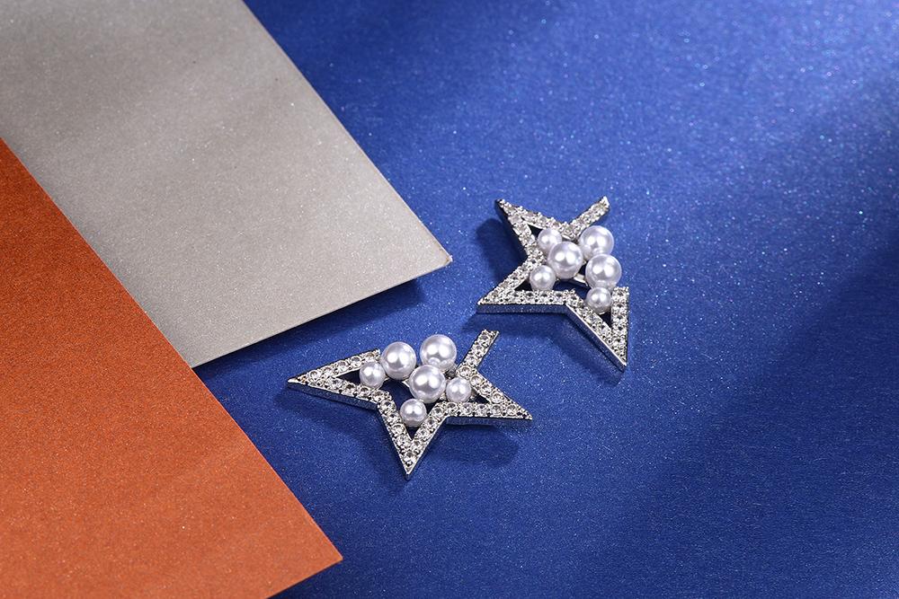個性幾何簍空珍珠 耳針/黏式耳環,桌上展示。