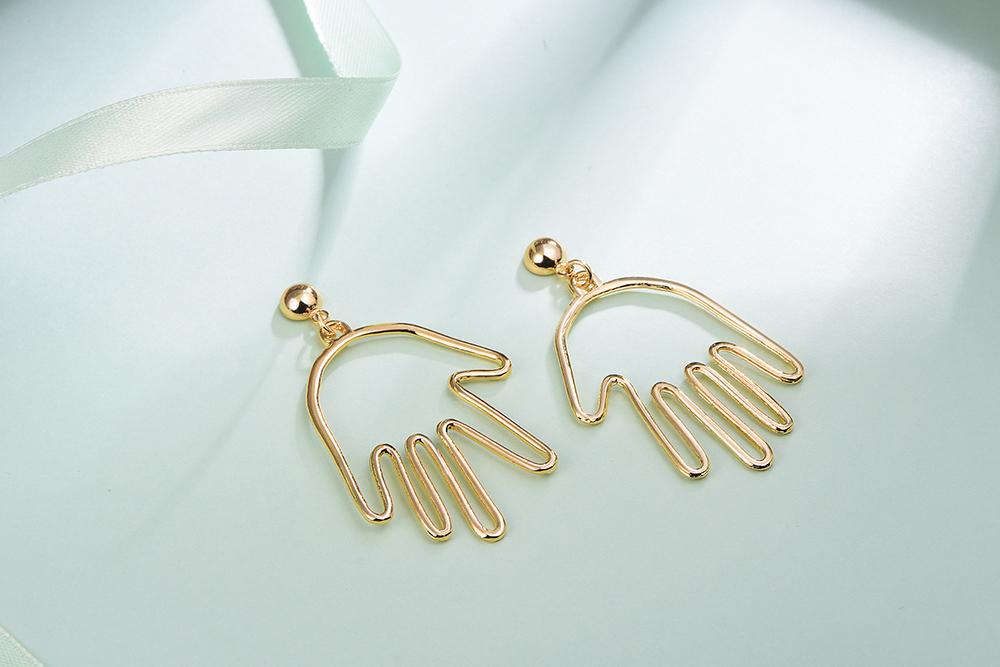 個性簍空手掌合金黏式耳環,桌上展示。