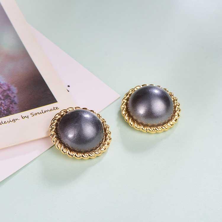 簡約復古灰色大珍珠黏式耳環,桌上展示。