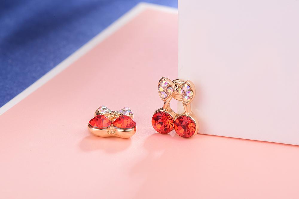 甜美可愛蝴蝶結櫻桃黏式耳環,桌上展示。