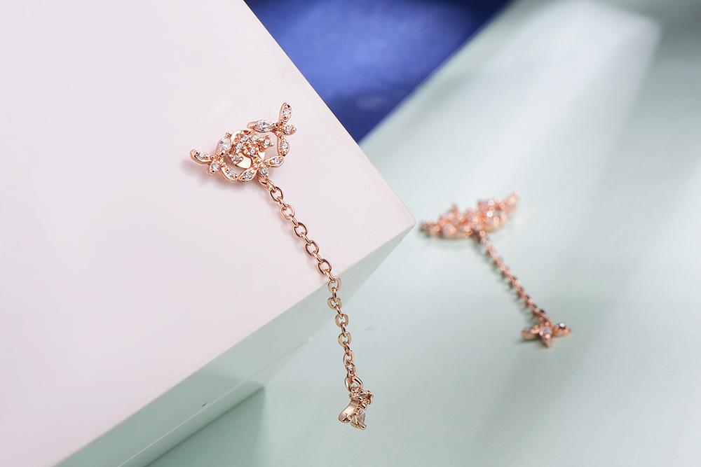 氣質簍空花卉流蘇黏式耳環,桌上展示。