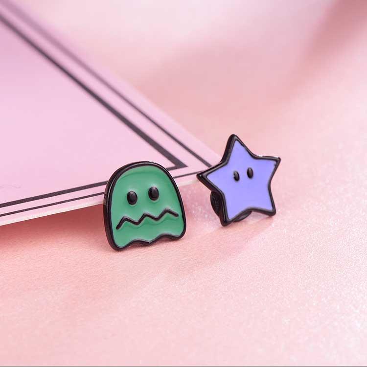 經典小精靈系列不對稱黏式耳環,桌上展示。