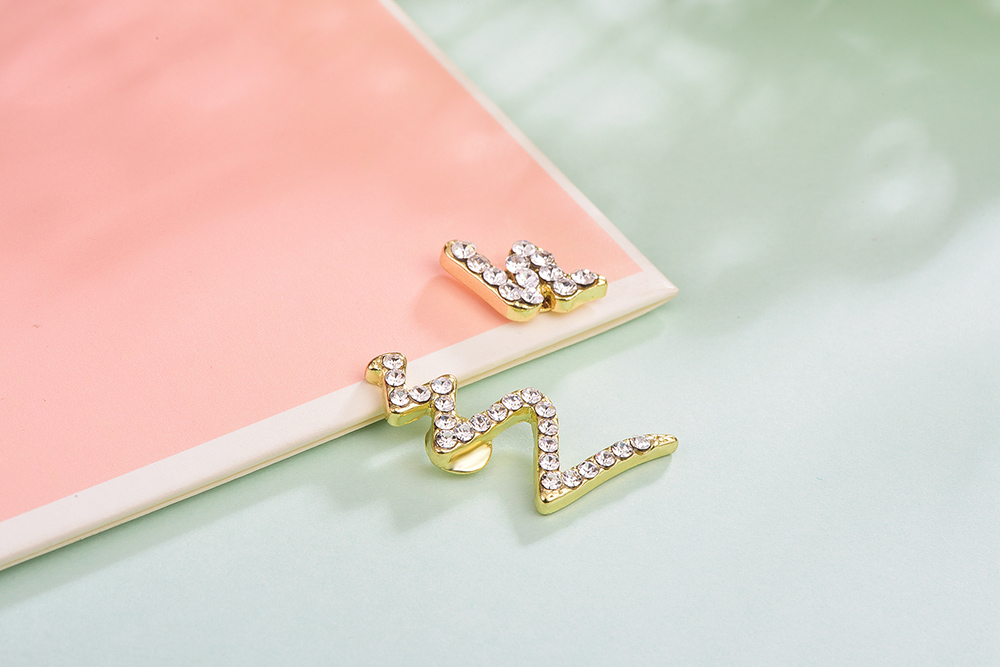 個性不對稱蛇形鋯鑽黏式耳環,桌上展示。