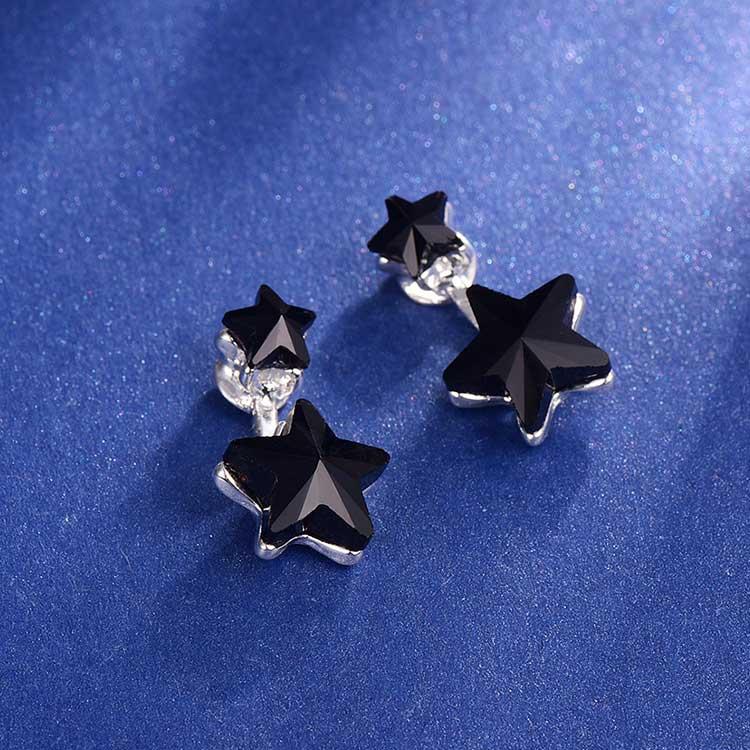 優雅亮黑五角星星 耳針/黏式耳環,桌上展示。