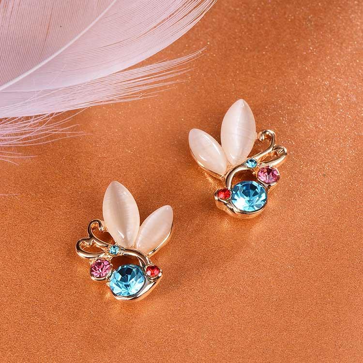 鑲鑽貓眼石蝴蝶黏式耳環,桌上展示。