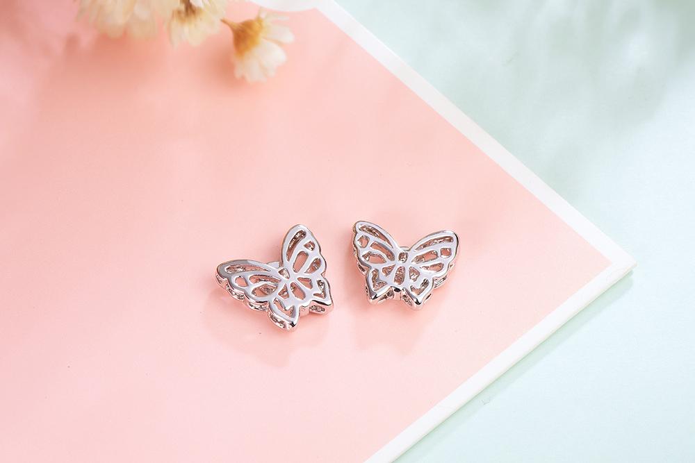 雙層立體簍空蝴蝶黏式耳環,桌上展示。
