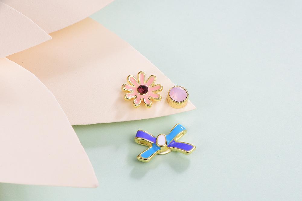迷你可愛小雛菊不對稱黏式耳環,桌上展示。