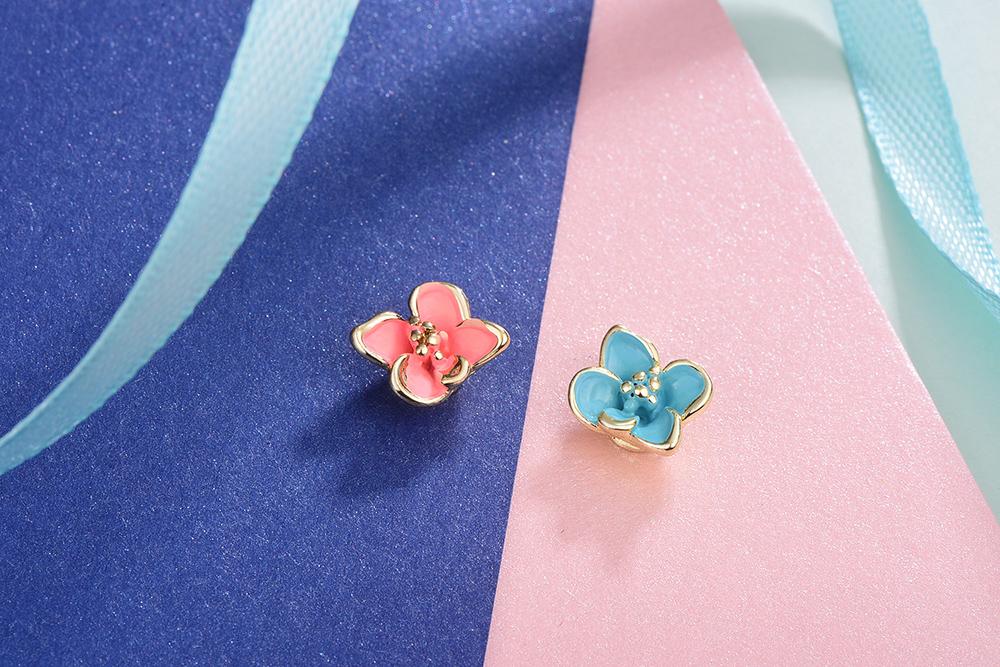 迷你可愛粉嫩花朵不對稱黏式耳環,桌上展示。