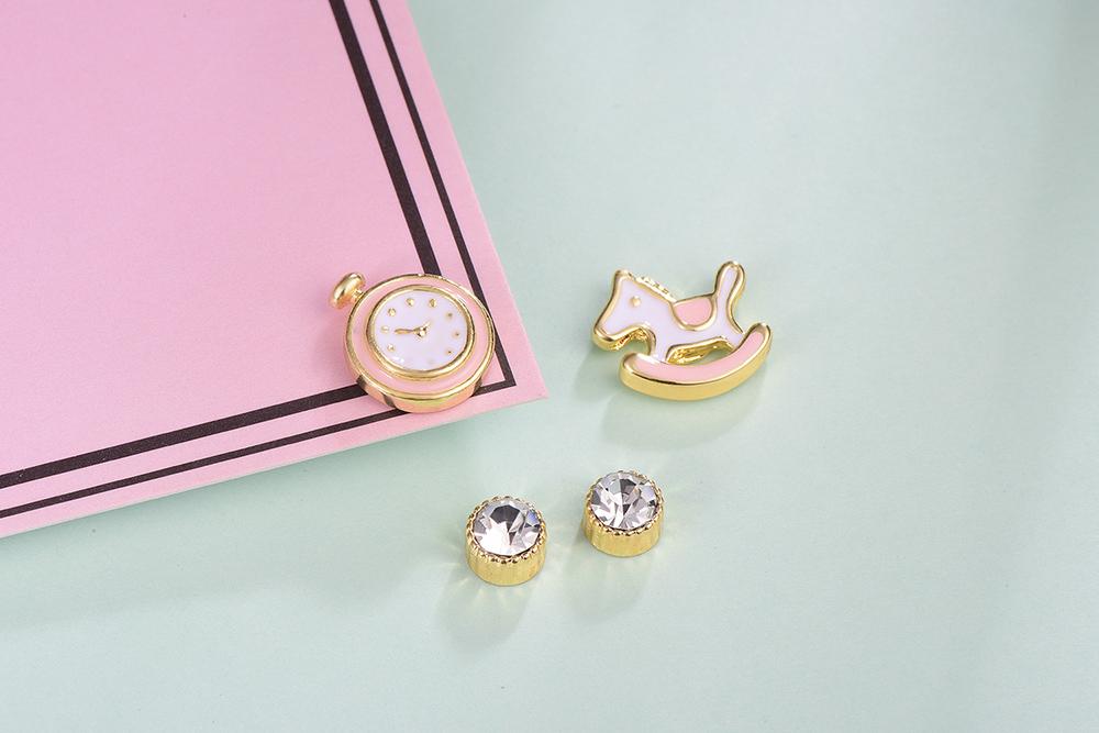 童趣鬧鐘木馬水鑽不對稱黏式耳環,桌上展示。