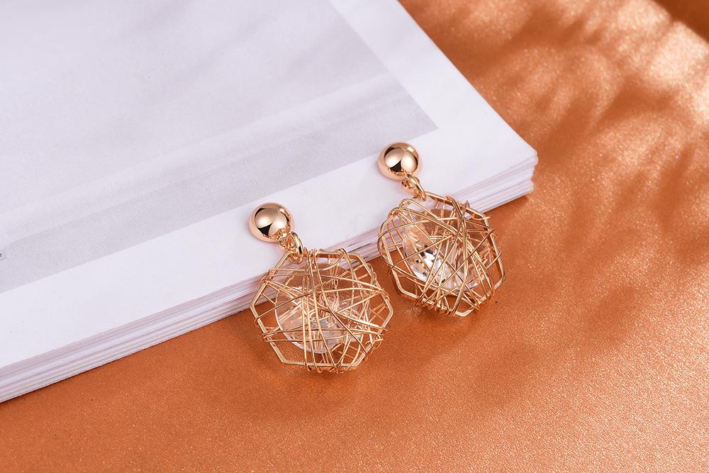 六角鐵絲纏繞水鑽黏式耳環,桌上展示。