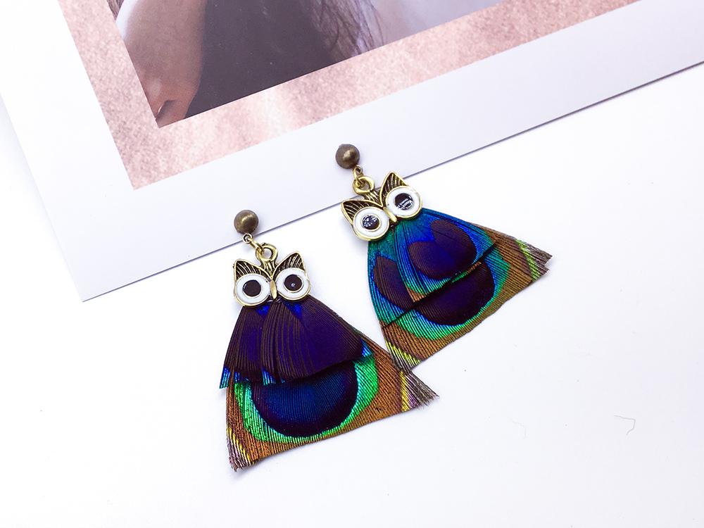 彩色羽毛貓頭鷹黏式耳環,桌上展示。