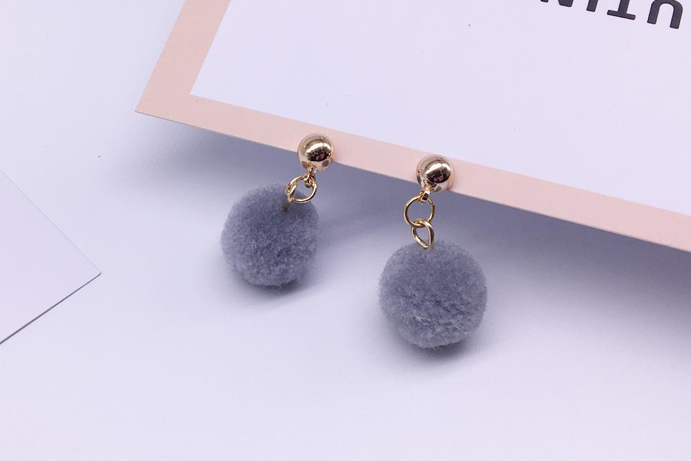 時尚純色毛球黏式耳環,桌上展示。