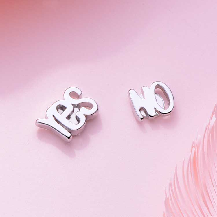 個性英文字母黏式耳環,桌上展示。