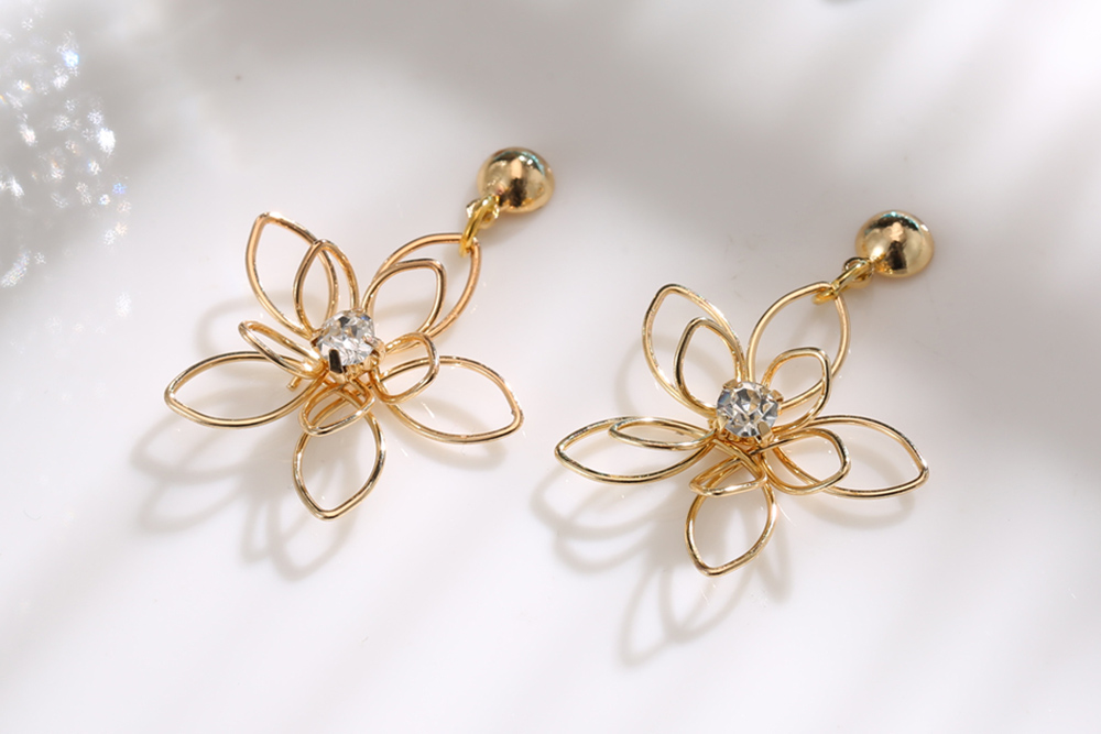 氣質立體編織簍空花朵黏式耳環,桌上展示。