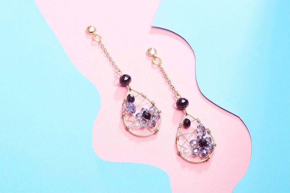 水滴金屬纏線鑲鑽 耳針/黏式耳環,桌上展示。