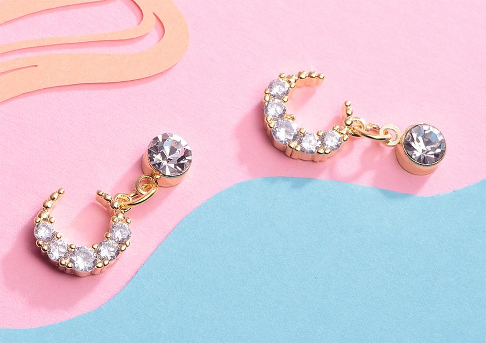 耀眼鑲鑽月亮黏式耳環,桌上展示。