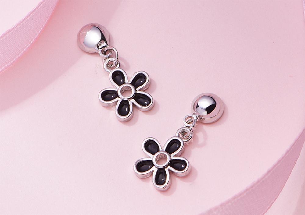 優雅黑色雛菊花朵 耳針/黏式耳環,桌上展示。