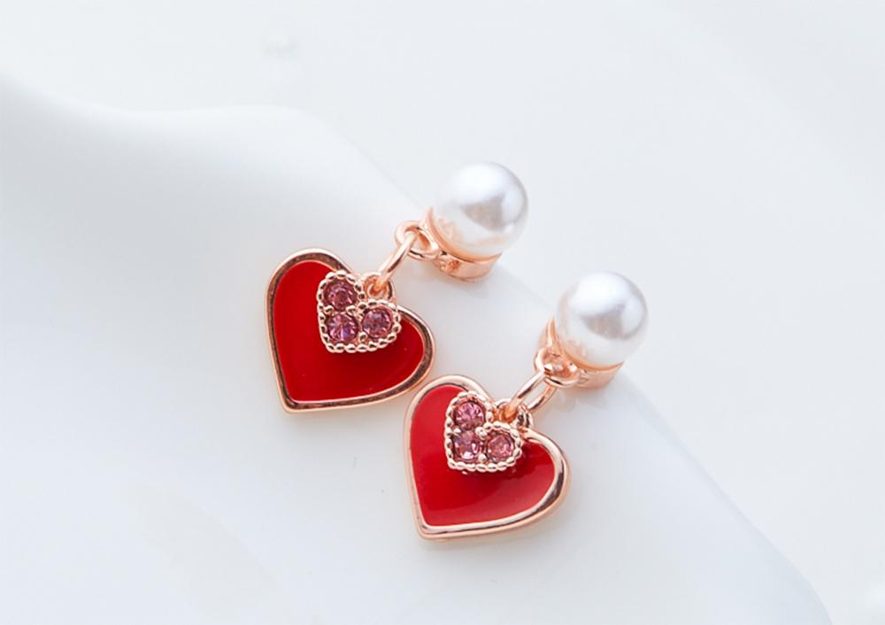 甜美心形珍珠 耳針/黏式耳環,桌上展示。